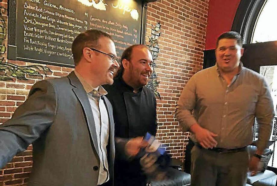From left, co-owners Matt Bailey, chef John Brennan and Erick Williams at the ribbon-cutting for the opening of Olives and Oil at the corner of Temple and Crown streets in New Haven. Photo: Mary O'Leary — New Haven Register