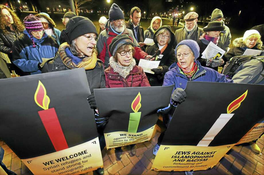 """New Haven residents, from left, Ginger Chapman, Ellen Rubin and Susan Bramhall sing """"Hannukah, oh Hannukah,"""" during a demonstration Wednesday in New Haven. Photo: Catherine Avalone — New Haven Register   / New Haven RegisterThe Middletown Press"""
