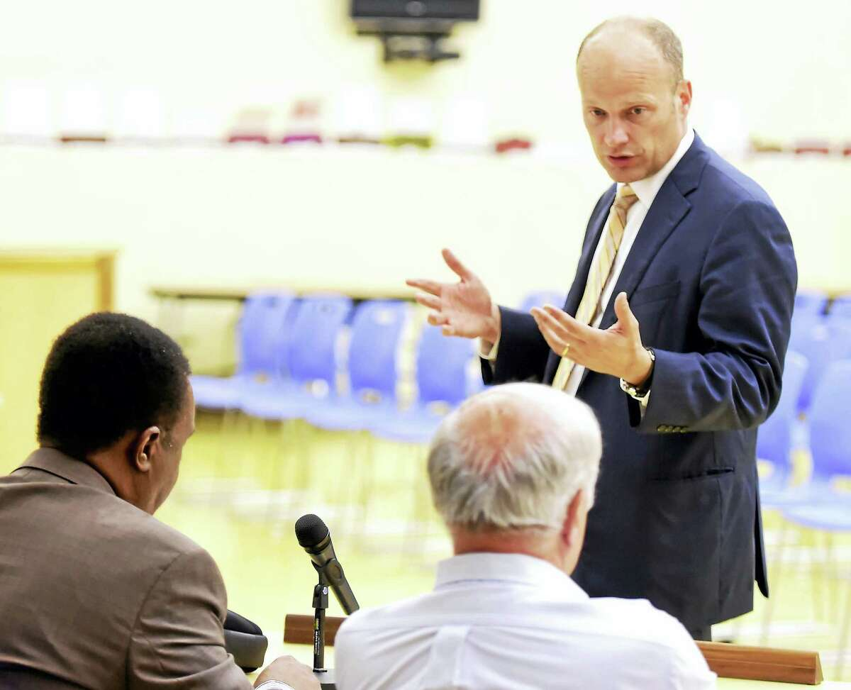 New Haven Superintendent of Schools Garth Harries talks with New Haven School Board members Michael R. Nast, right, and Dr. Edward Joyner, left.