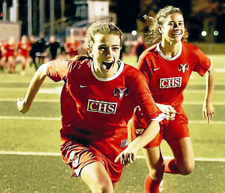 Cheshire senior midfielder Allison Leonetti, left, and senior forward Saige Bingman rush to celebrate with their teammates after defeating Daniel Hand, 5-4, in penalty kicks for the SCC soccer championship Thursday at West Haven High School. Photo: Catherine Avalone — New Haven Register