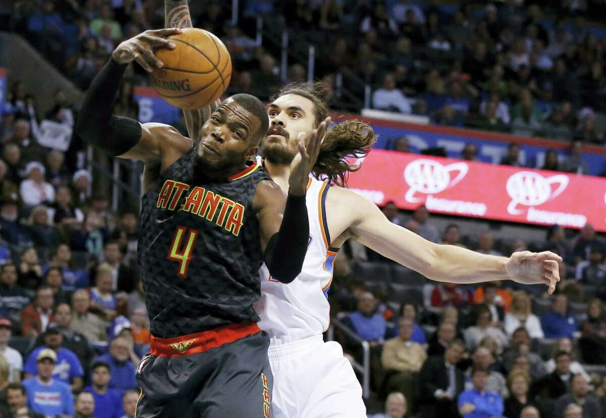 Atlanta Hawks forward Paul Millsap (4) grabs a rebound in front of Oklahoma City Thunder center Steven Adams, right, in the first half of an NBA basketball game in Oklahoma City on Monday, Dec. 19, 2016.