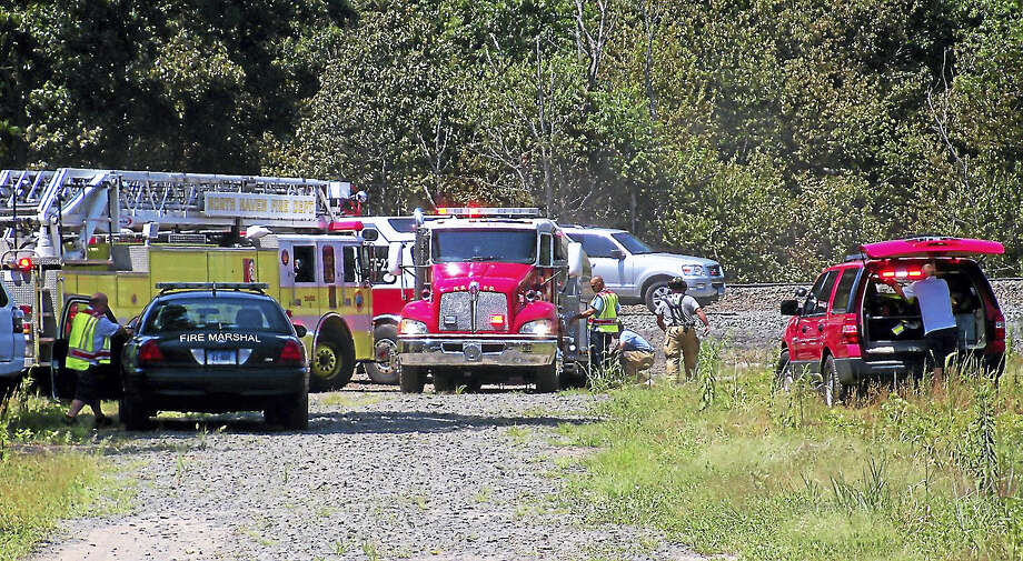Firefighters from North Haven and Hamden worked for more than an hour Monday to contain a brush fire along the railroad tracks near part of Washington Avenue in North Haven. Photo: Wes Duplantier — The New Haven Register