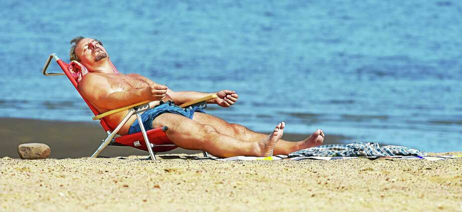 John Bodnar works on his tan at the beach in West Haven last year. Photo: New Haven Register File Photo   / New Haven RegisterThe Middletown Press