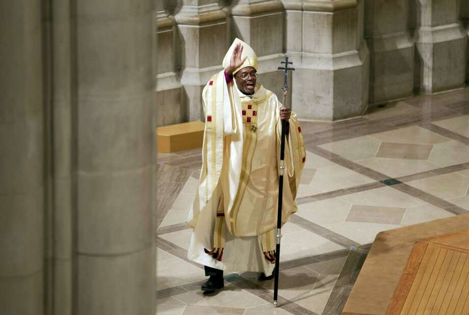 In this Nov. 1, 2015 photo, Episcopal Church Presiding Bishop Michael Curry waves to the crowd after Mass at the Washington National Cathedral in Washington. Curry, the church's first black leader, was elected in June 2015 to succeed Presiding Bishop Katharine Jefferts Schori, the first woman leader of the church. Photo: AP Photo/Jose Luis Magana   / FR159526 AP