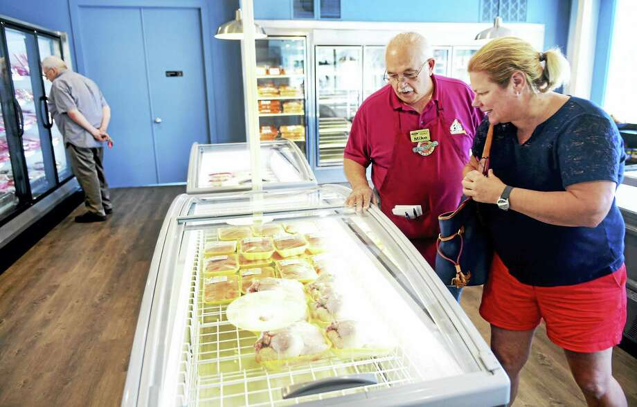 Ferraro's Market employee Mike Fimiani shows Meg Hayden of Madison some of the stock at the market's new Madison location that opened Friday. Photo: Peter Hvizdak — New Haven Register   / ©2016 Peter Hvizdak-