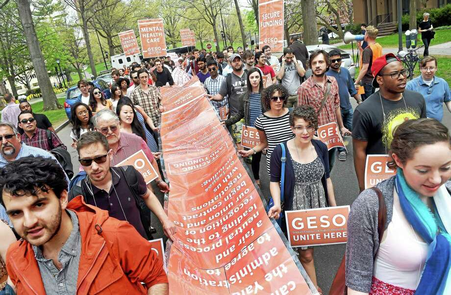 GESO members and supporters carry a petition calling on Yale University to negotiate on issues of secure pay, mental health services and racial and gender equity as they march down march down Hillhouse Avenue in New Haven in May 2015. Photo: Arnold Gold — New Haven Register File Photo