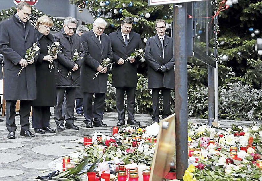 German officials attend a flower ceremony at the Kaiser Wilhelm Memorial Church in Berlin, Germany, Tuesday. Photo: Michael Solm — AP