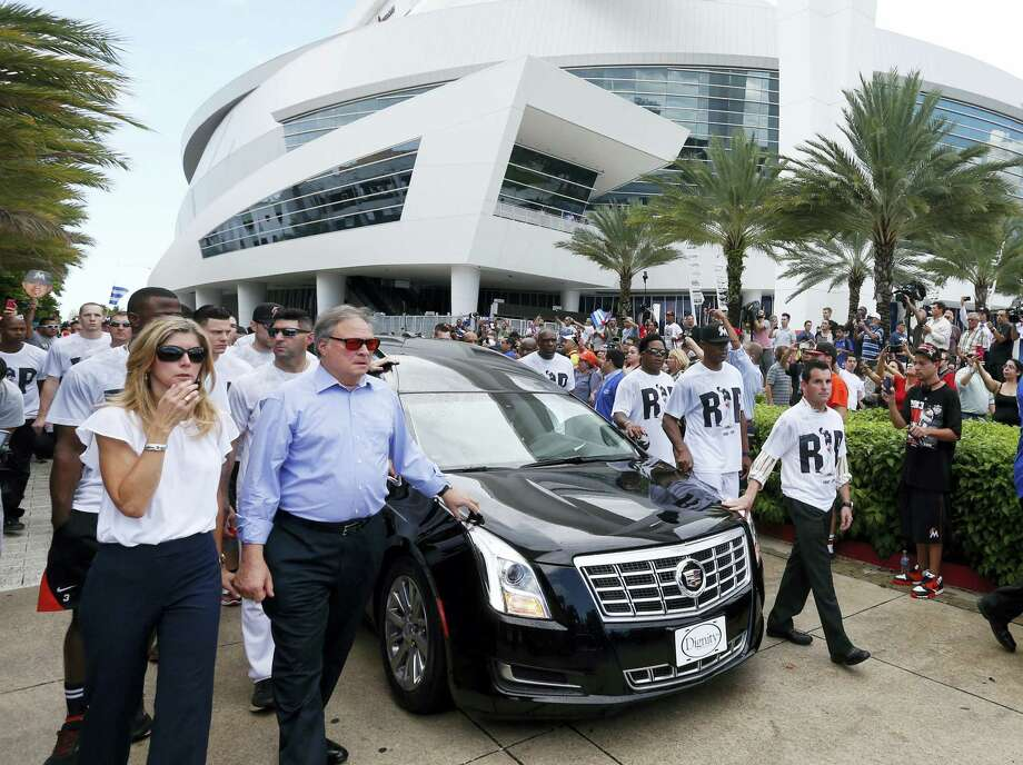 Miami Marlins owner and CEO Jeffrey Loria, second left, and Marlins president David Samson, right, lead players and staff as they escort a hearse carrying the body of pitcher Jose Fernandez as it leaves Marlins Park stadium Wednesday in Miami. Fernandez was killed in a weekend boat crash along with two friends. Photo: WILFREDO LEE — The Associated Press   / Copyright 2016 The Associated Press. All rights reserved.