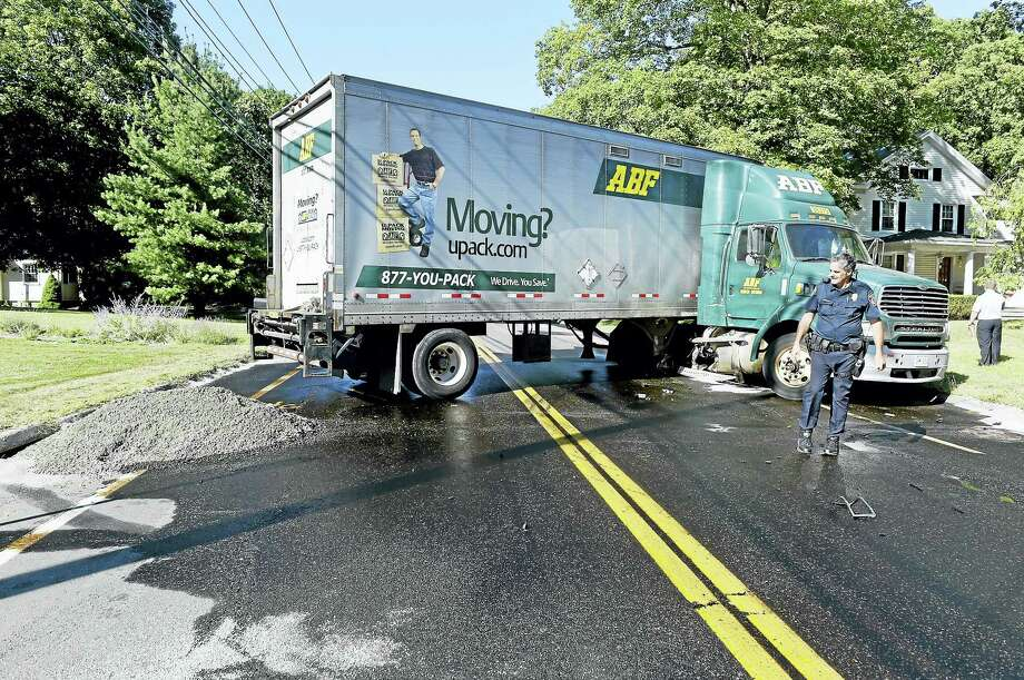 North Haven police Officer Ted Stockman inspects a truck hauling wire cable on Quinnipiac Avenue after the truck was hit by a car exiting Vincent Street in North Haven Monday afternoon. Photo: Peter Hvizdak — New Haven Register   / ©2016 Peter Hvizdak
