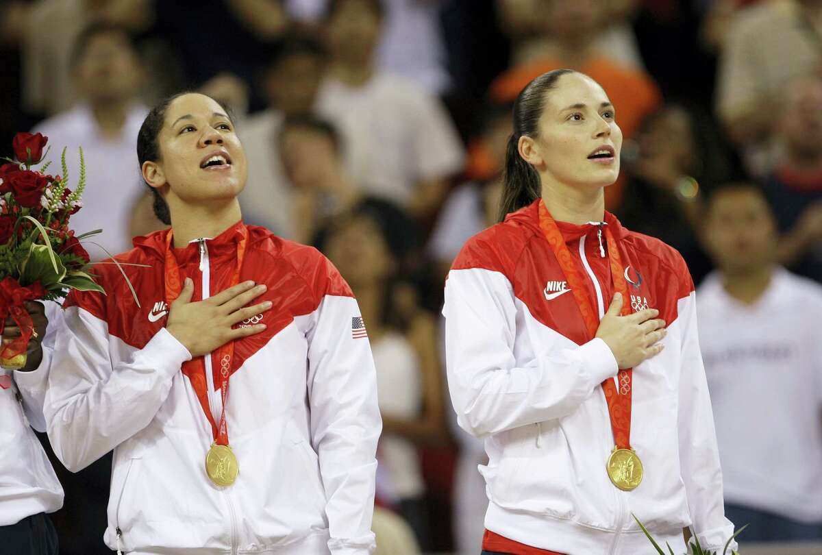 In this Aug. 23, 2008 photo, Kara Lawson left, and Sue Bird, both of the United States, sing their national anthem during the gold medal ceremony for women's basketball at the Beijing 2008 Olympics. Bird is aiming for her fourth gold medal in Rio.