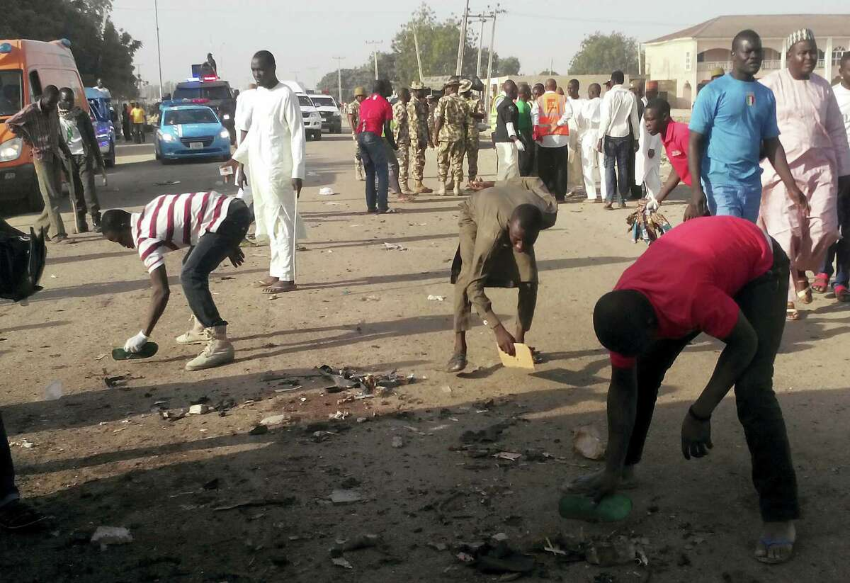 People clear debris after an explosion in Maiduguri, Nigeria, Saturday, Oct. 29, 2016. Twin explosions from female suicide bombers suspected to be with Boko Haram killed nine people and injured more than 20 in Nigeria's northeastern city of Maiduguri on Saturday morning, officials and witnesses said.