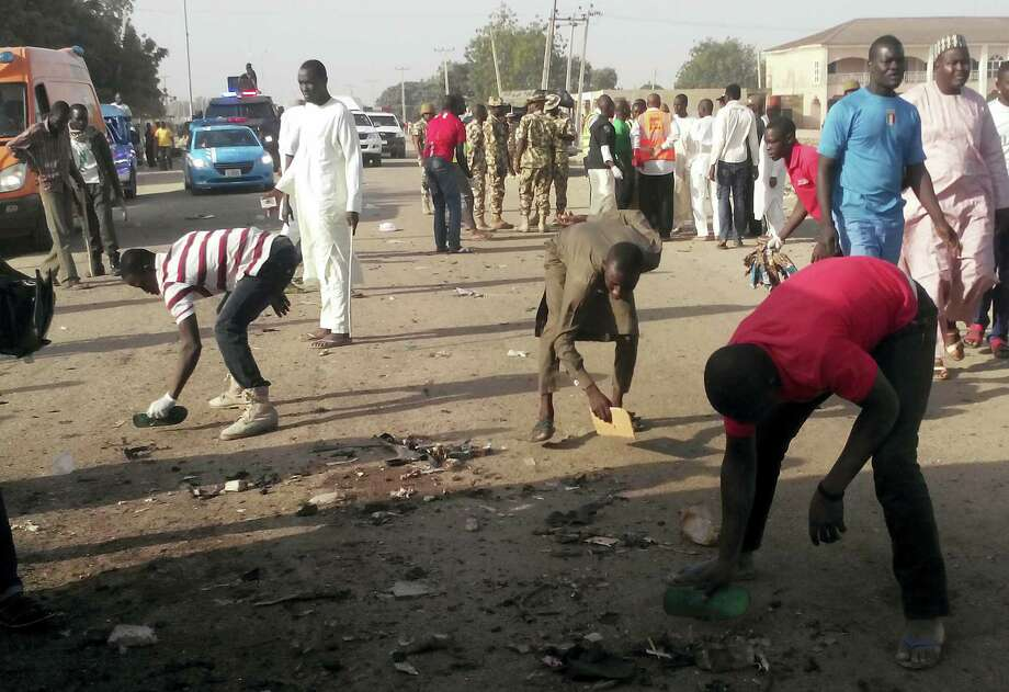People clear debris after an explosion in Maiduguri, Nigeria, Saturday, Oct. 29, 2016. Twin explosions from female suicide bombers suspected to be with Boko Haram killed nine people and injured more than 20 in Nigeria's northeastern city of Maiduguri on Saturday morning, officials and witnesses said. Photo: AP Photo/Jossy Ola    / Copyright 2016 The Associated Press. All rights reserved.