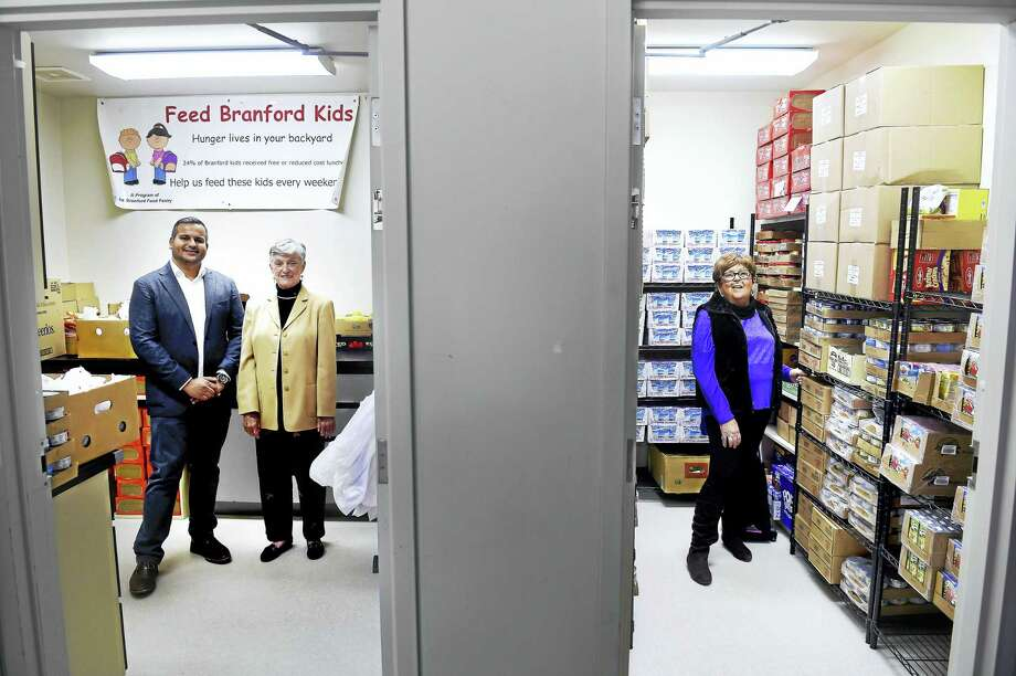 From left, Diamond Sponsor Kamran Farid, volunteer Susan Barnes and Johanne Pantani, founder of Feed Branford Kids, are photographed in the operation's warehouse in Branford Friday. Photo: Arnold Gold — New Haven Register