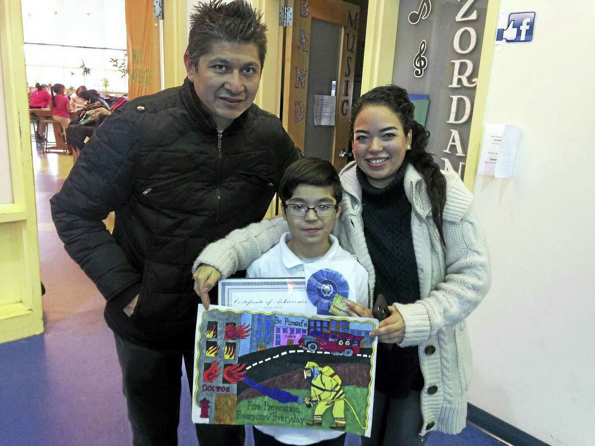 Fourth-grade contest winner Jorge Rodriguez with his parents, Jorge and Yadira Rodriguez.