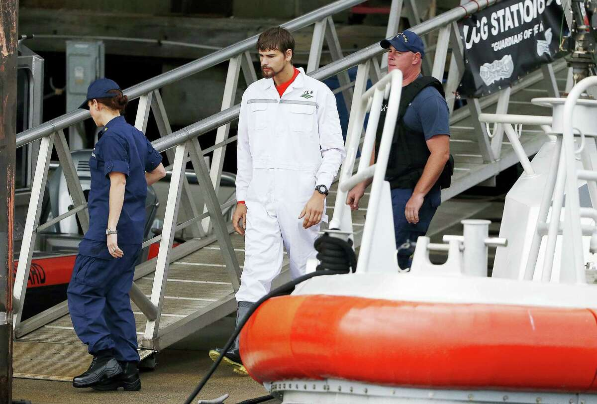 Nathan Carman, center, disembarks from a small boat at the U.S. Coast Guard station in Boston Tuesday.
