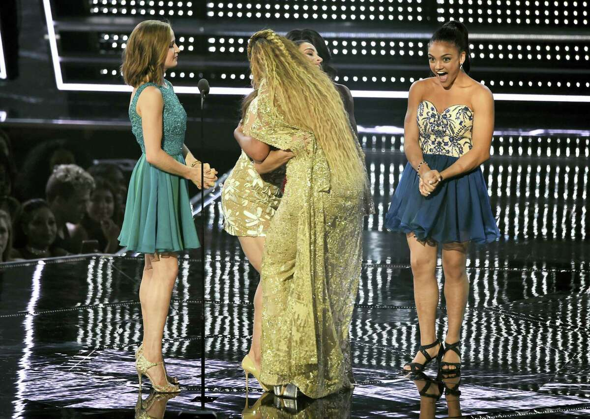 Beyonce, center, embraces U.S. Olympic gymnast Aly Raisman as fellow gymnasts Madison Kocian, left, and Laurie Hernandez, right, look on after Beyonce was presented with the award for best female video at the MTV Video Music Awards at Madison Square Garden on Aug. 28, 2016 in New York.