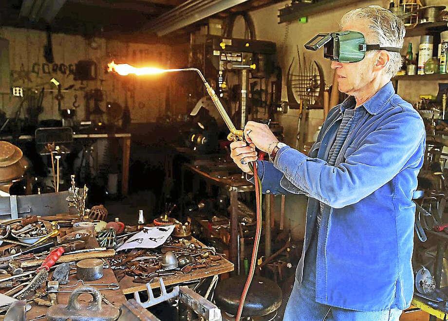 Stuart Alan Lerner, a found object metal sculptor, uses an acetylene torch in his home workshop in Madison. Photo: Peter Hvizdak — New Haven Register   / ?2016 Peter Hvizdak