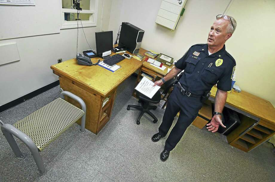 Ansonia Police Chief Kevin Hale in the booking room by an old makeshift desk at police headquarters, Wednesday, October 19, 2016, during a public tour of the antiquated facility, built in 1894 as the former Larkin School. The city of Ansonia is asking voters to approve a new $12 million facility during a November 8 referendum. Photo: Catherine Avalone — New Haven Register / New Haven RegisterThe Middletown Press