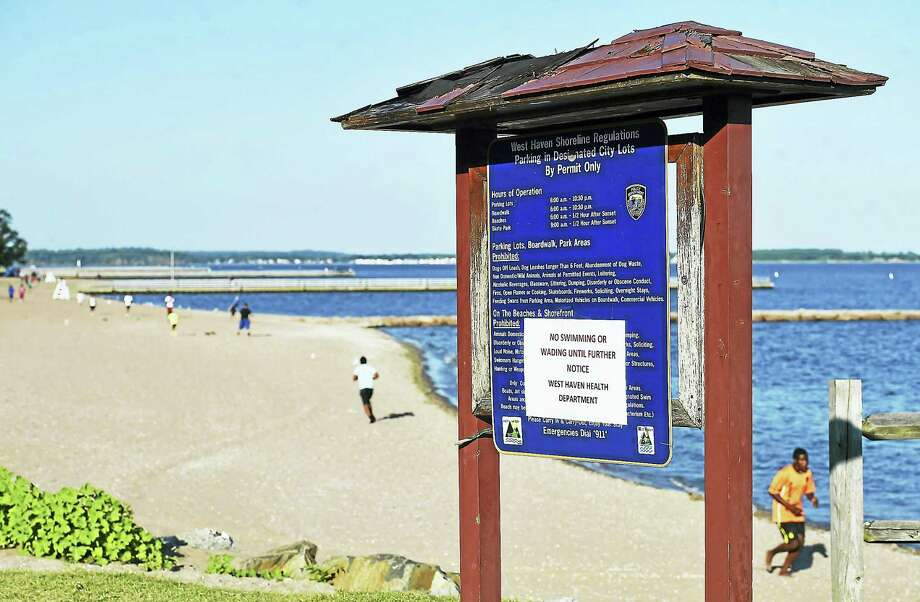 The West Haven Health Department posted notices Wednesday on the kiosks at the beach at Savin Rock telling people not to go in the water. Photo: Catherine Avalone — New Haven Register   / New Haven RegisterThe Middletown Press