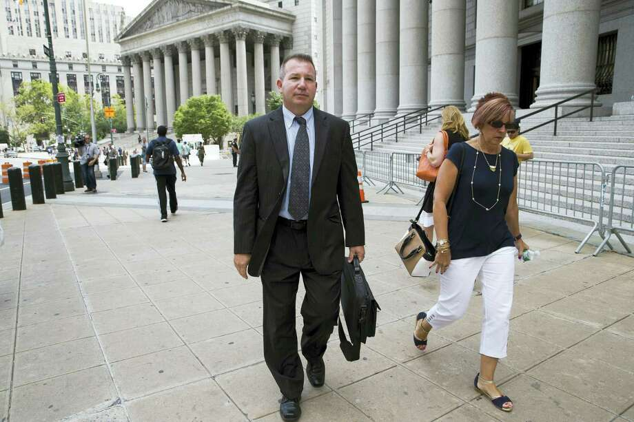 """In this July 13, 2016 photo, retired New York Police Department Sgt. Ronald Buell, center, leaves federal district court in Manhattan. Buell received probation for selling National Crime and Information Center information to a private investigator for defense attorneys. At his sentencing, Buell said he hoped other officers would learn """"to never put themselves in the position I'm in."""" Photo: AP Photo/Mary Altaffer   / Copyright 2016 The Associated Press. All rights reserved. This material may not be published, broadcast, rewritten or redistribu"""