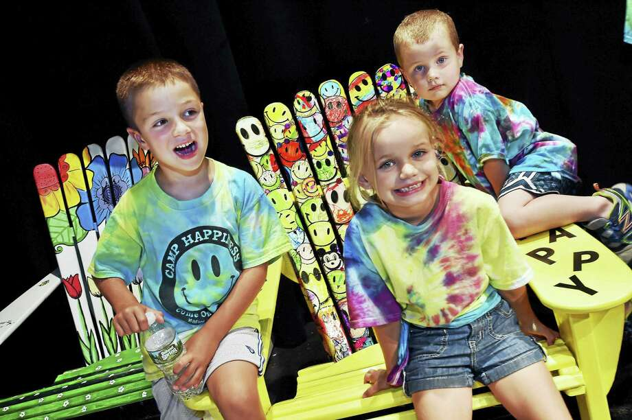 Children flock to the Camp Happiness Adirondack chair at the Milford Education Foundation Chair-ity Auction 2016 Kickoff Tuesday at the Milford Arts Council. Photo: Catherine Avalone — New Haven Register   / New Haven RegisterThe Middletown Press