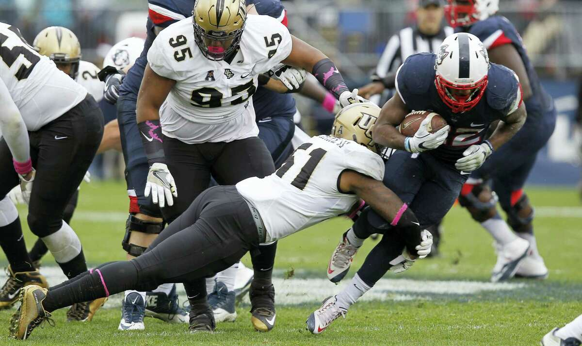UConn running back Arkeel Newsome, right, looks to break a tackle during last week's game against UCF.