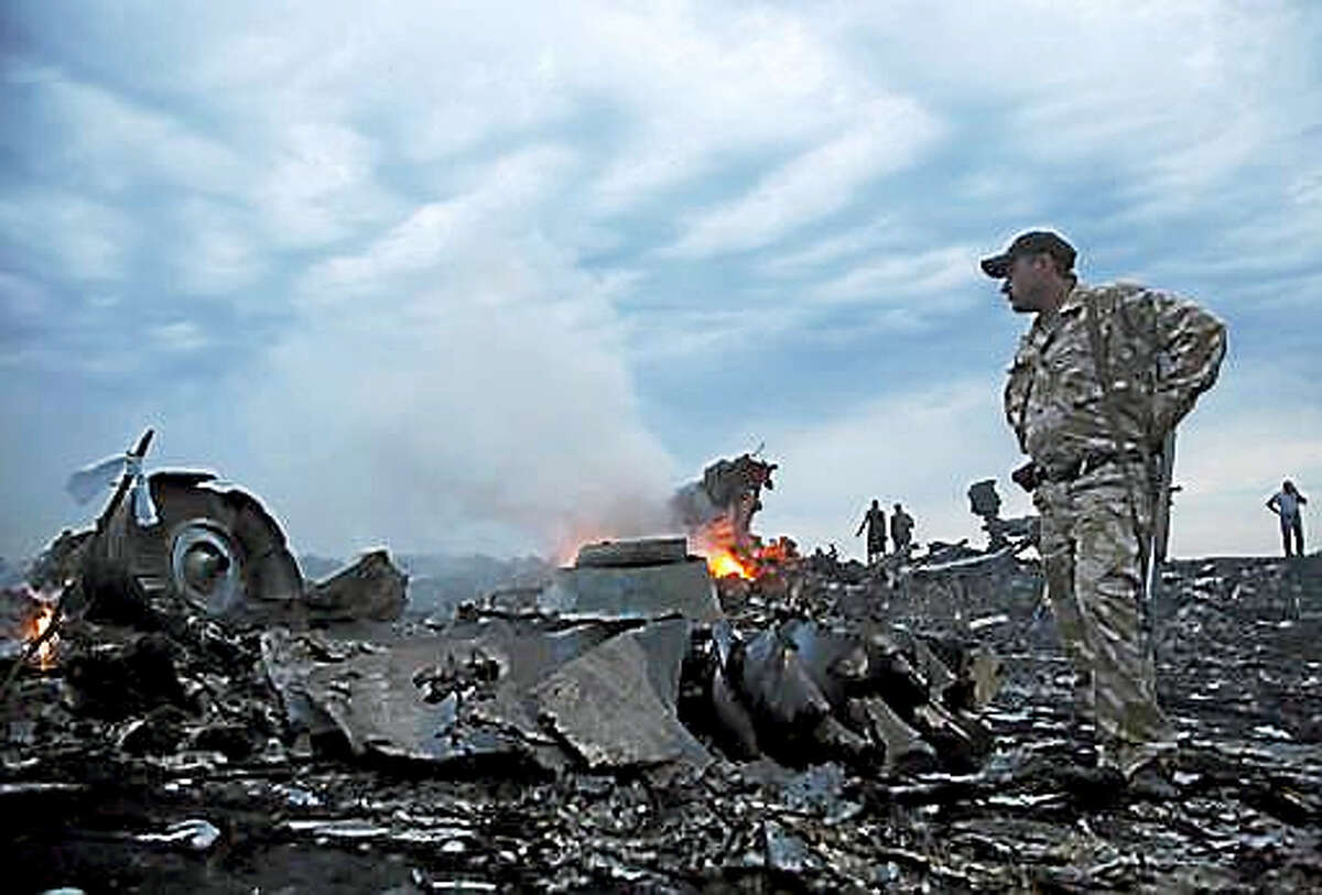 In this Thursday, July 17, 2014, file photo, people walk amongst the debris, at the crash site of a passenger plane near the village of Grabovo, Ukraine. Relatives of victims of the shooting-down of a Malaysia Airlines jetliner over Ukraine more than two years ago were gathering Wednesday, Sept. 28, 2016, to learn the preliminary results of a Dutch-led criminal probe of the disaster that claimed 298 lives.