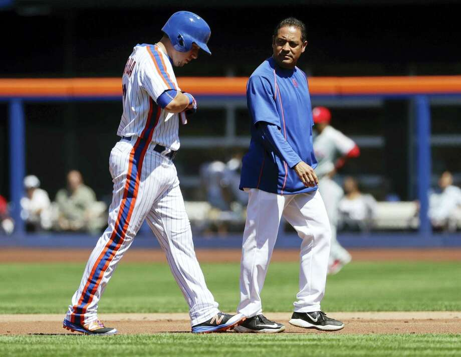 A trainer walks the Mets' Asdrubal Cabrera, left, off the field in the first inning on Sunday. Photo: Frank Franklin II — The Associated Press   / Copyright 2016 The Associated Press. All rights reserved. This material may not be published, broadcast, rewritten or redistribu