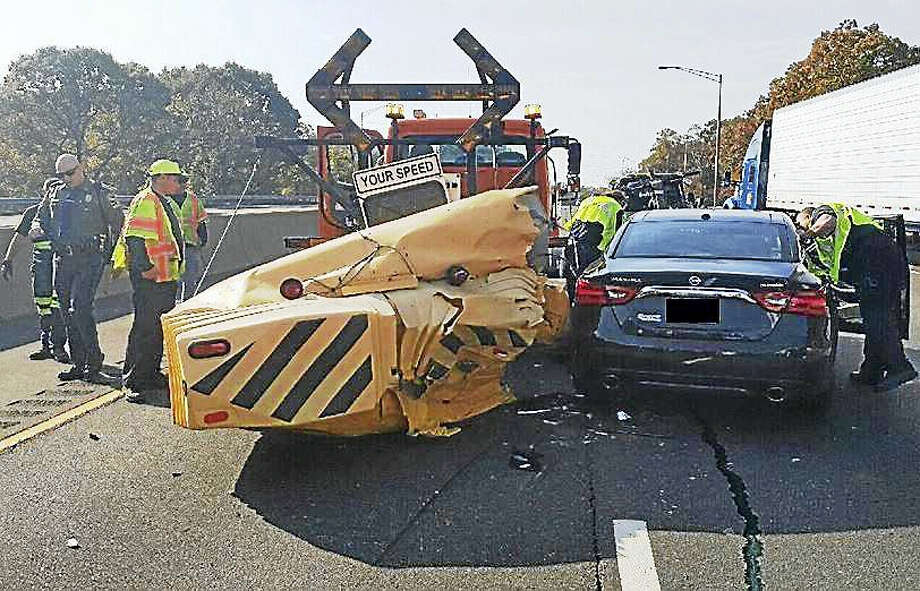 Two people were taken to the hospital Wednesday after their car crashed into the back of a state construction vehicle on Interstate 95 in Milford. Police are reminding people they must slow down and move over if they see the trucks stopped on the highway. Photo: Courtesy Of Connecticut State Police