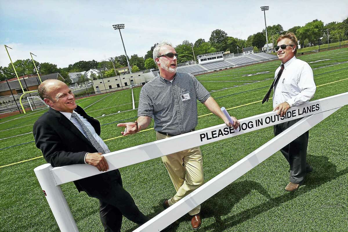 From left, New Haven Public Superintendent of Schools Garth Harries, Chief Operations Officer Will Clark, and SLAM Collaborative Design Principal Glenn Gollenberg speak during a walking tour at the recently restored Bowen Field in New Haven Thursday.
