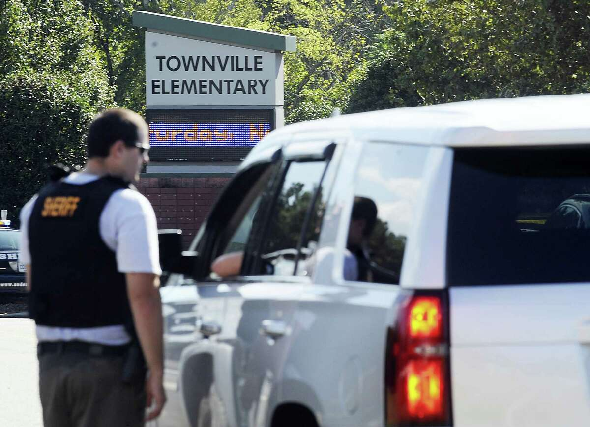 Members of law enforcement talk in front of Townville Elementary School on Wednesday, Sept. 28, 2016, in Townville, S.C. A teenager opened fire at the South Carolina elementary school Wednesday, wounding two students and a teacher before the suspect was taken into custody, authorities said.