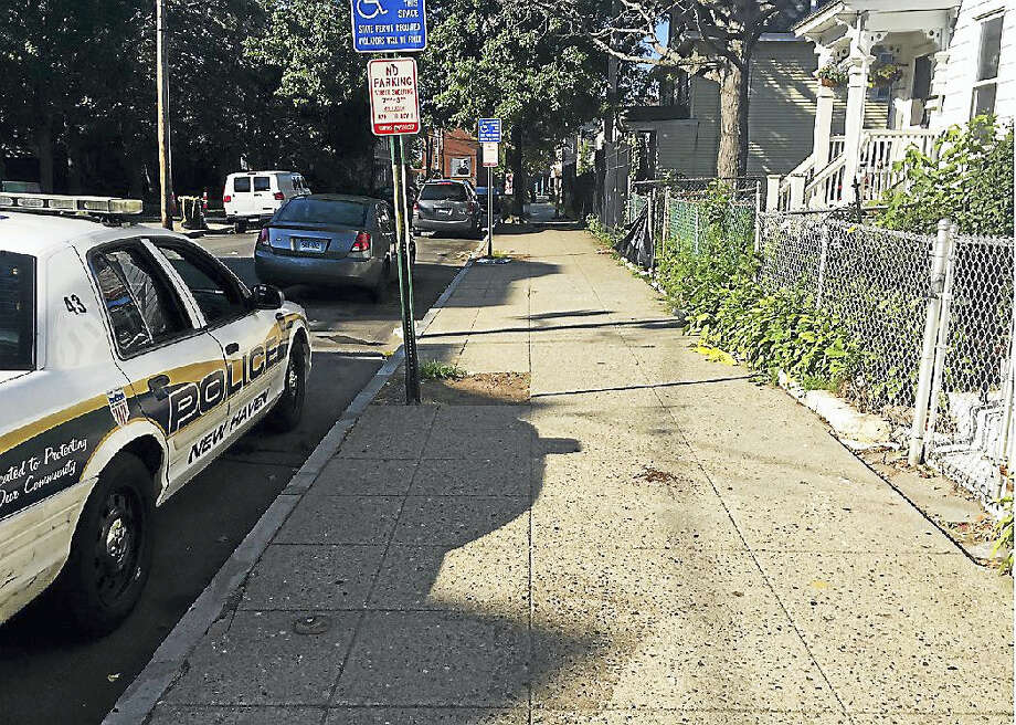A police car and a piece of yellow police tape on the ground mark the scene of a homicide early Saturday morning on Kensington Street in New Haven. Photo: Brian Zahn — New Haven Register