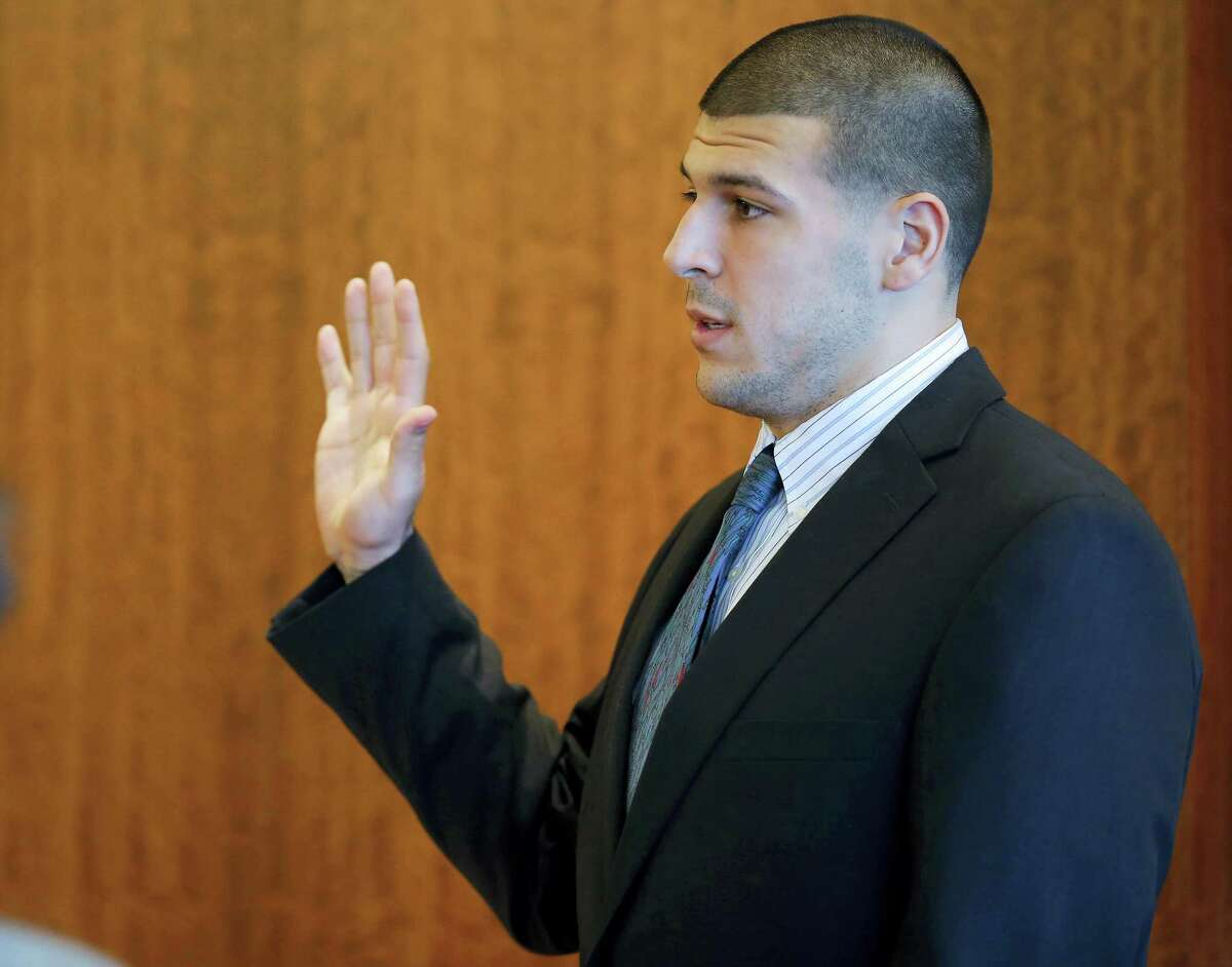 Former New England Patriots NFL football player Aaron Hernandez takes an oath during a pretrial court hearing in Fall River, Mass. on Wednesday, Oct. 9, 2013. Hernandez was indicted in August in the killing of 27-year-old Odin Lloyd, a semi-professional football player from Boston who was dating the sister of Hernandez's girlfriend. He has pleaded not guilty.