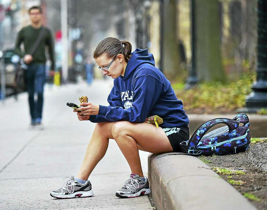 New Jersey resident Tori Campbell, a senior at Yale University majoring in english and educational studies, sits on Chapel Street in New Haven, enjoying an ice cream. Photo: Catherine Avalone — New Haven Register/file   / New Haven RegisterThe Middletown Press