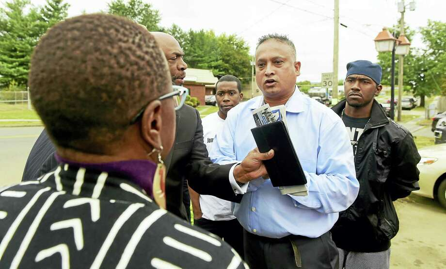Fazlay Rabbi, owner of Slyce Pizza & Bar restaurant, second from right, is held back by Anthony Bennett, co-chairman of CONECT and pastor of Mount Aery Baptist Church in Bridgeport, as he tries to give his condolences to Odell Cooper of New Haven, mother of homicide victim Jonathan Cooper, after a press conference Wednesday in front of Slyce Pizza & Bar in Hamden. Photo: Peter Hvizdak — New Haven Register   / ?2016 Peter Hvizdak