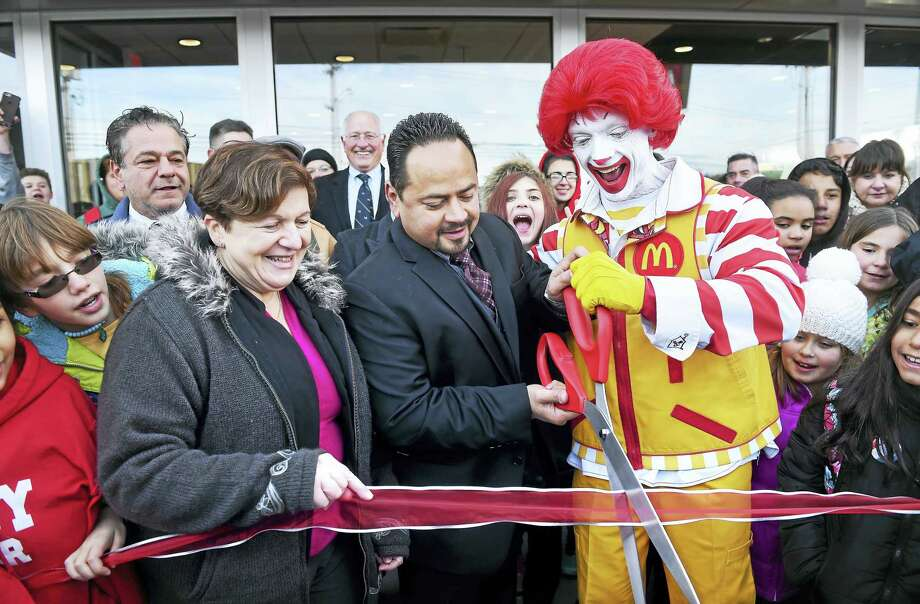From left, Derby Mayor Anita Dugatto, McDonald's owner/operator Joe Rodriguez and Ronald McDonald cut a ribbon for the grand re-opening of McDonald's on Division Street in Derby Monday. In the background at left is Ansonia Mayor David Cassetti. Photo: Arnold Gold — New Haven Register