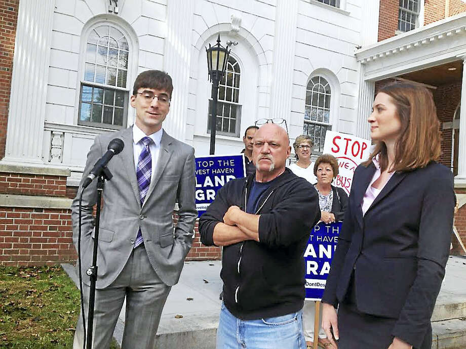 Attorney Robert McNamara, left, of the Institute for Justice talks about a lawsuit filed Tuesday on behalf of The Haven holdout Robert McGinnity, center, and his family. The suit alleges the city of West Haven is abusing the eminent domain process in seeking to acquire two properties the McGinnity's own on First Avenue. Also in the photo are Institute for Justice attorney Renee Flaherty, at right; Saed Ahmed, one of the owners of the Citgo station at First and Elm streets, who filed a similar lawsuit, just to McGinnity's left; McGinnity's sister, Gloria Murphy, and, at rear, supporter Patricia Bollettieri. Photo: MARK ZARETSKZY — NEW HAVEN REGISTER
