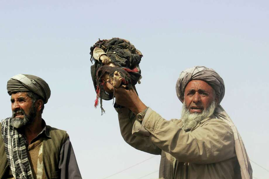 An Afghan man holds up the body of a child that was killed during clashes between Taliban and Afghan security forces in Kunduz province north of Kabul, Afghanistan on Nov. 3, 2016. Authorities say a joint raid by U.S. and Afghan forces targeting senior Taliban commanders killed two American service members and 26 civilians. Afghan officials said they were still investigating the attack and its civilian casualties, some of which may have been caused by the airstrikes. Photo: AP Photo/Najim Rahim   / Copyright 2016 The Associated Press. All rights reserved.