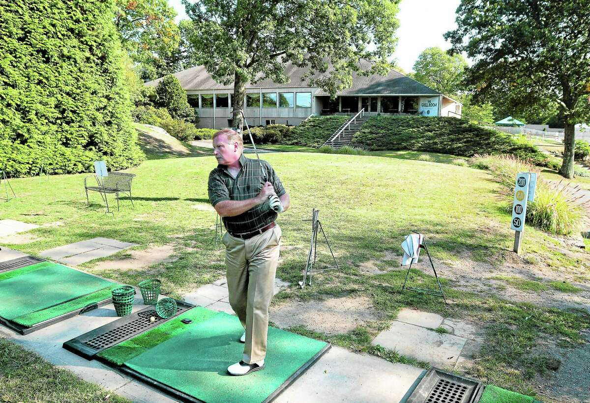 Bruce Blakeley of Wallingford hits golf balls at the Country Club of Woodbridge driving range.