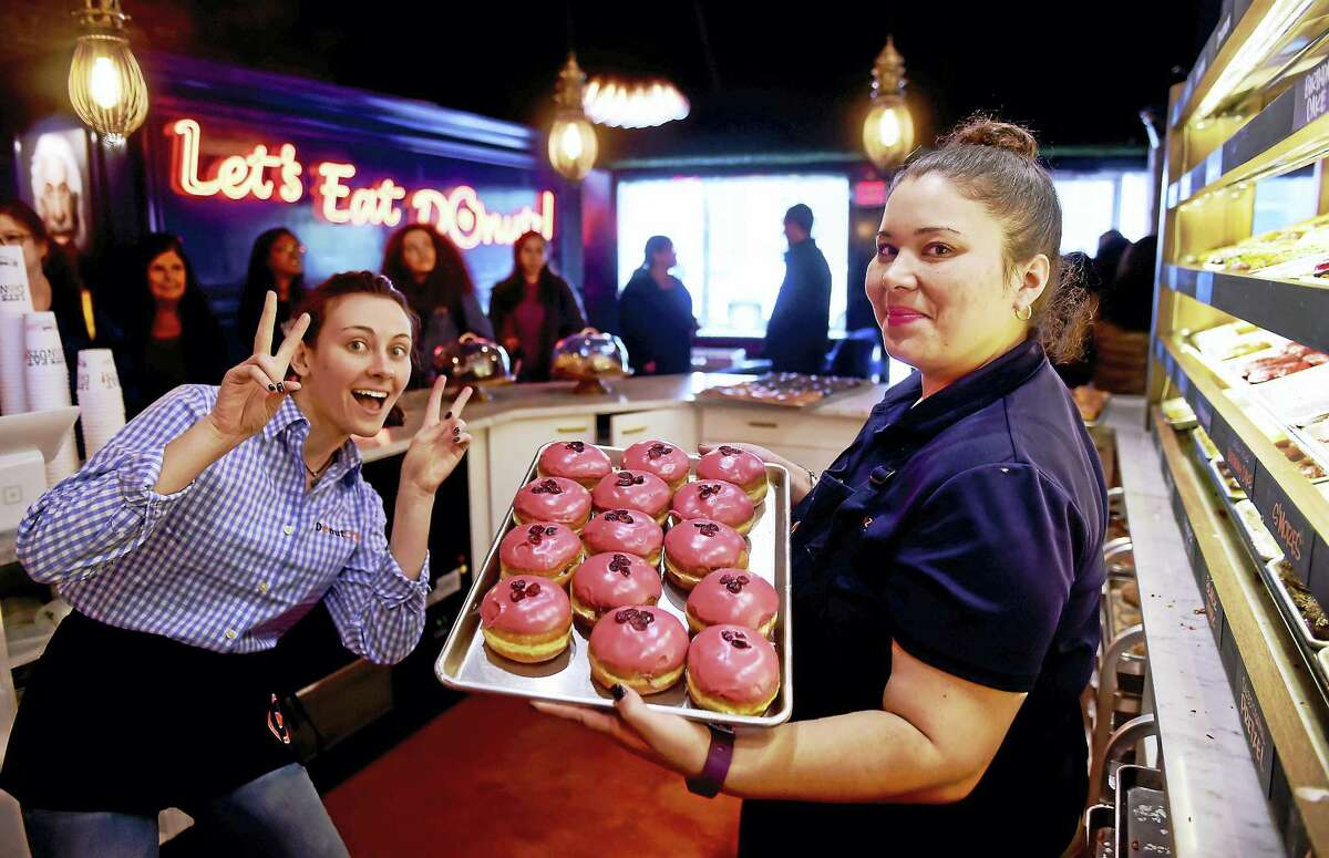Donut Crazy employees Michaela Murphy, left, and Rita Torres show of a batch of donuts at the new Donut Crazy doughnut shop on York Street in New Haven Friday.