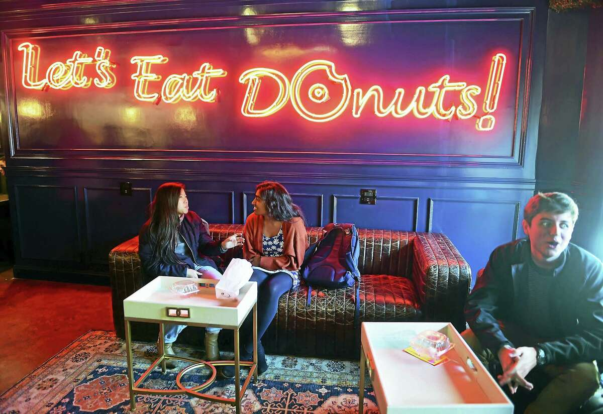 Yale students Levi Truong, Nitya Rayapati and Timothy White, left to right, relax after eating donuts at the new Donut Crazy donut shop on York Street in New Haven Friday.