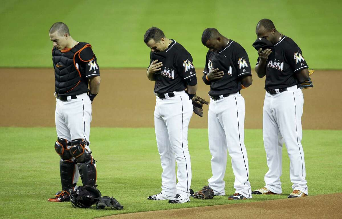 Miami Marlins catcher J.T. Realmuto, left, third baseman Martin Prado, second from left, shortstop Adeiny Hechavarria, second from right, and left fielder Marcell Ozuna, right, stand during a pre-game ceremony honoring pitcher Jose Fernandez before a baseball game against the New York Mets on Sept. 26, 2016 in Miami. Fernandez died in a boating accident Sunday.