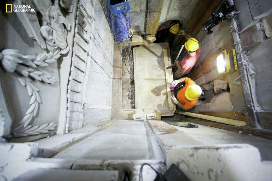 Workers remove the top marble layer of the tomb said to be of Jesus Christ, in the Church of Holy Sepulcher in Jerusalem. A restoration team has peeled away a marble layer for the first time in centuries in an effort to reach what it believes is the original rock surface where Jesus' body was laid. Photo: Dusan Vranic — National Geographic Via AP / National Geographic