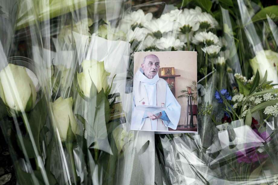 A picture of late Father Jacques Hamel is placed on flowers at the makeshift memorial in front of the city hall closed to the church where an hostage taking left a priest dead the day before in Saint-Etienne-du-Rouvray, Normandy, France, Wednesday, July 27, 2016. The Islamic State group crossed a new threshold Tuesday in its war against the West, as two of its followers targeted a church in Normandy, slitting the throat of an elderly priest celebrating Mass and using hostages as human shields before being shot by police. Photo: AP Photo/Francois Mori    / Copyright 2016 The Associated Press. All rights reserved. This material may not be published, broadcast, rewritten or redistribu
