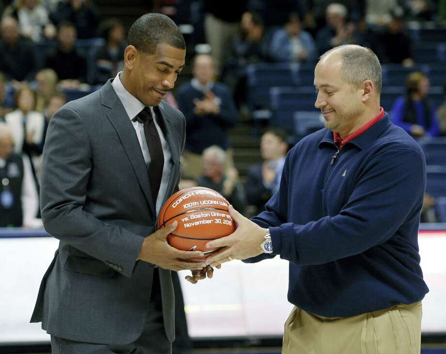 UConn head coach Kevin Ollie, left, is given a ball by athletic director David Benedict to honor his 100th win before Sunday's game in Storrs. Photo: Jessica Hill — The Associated Press   / AP2016