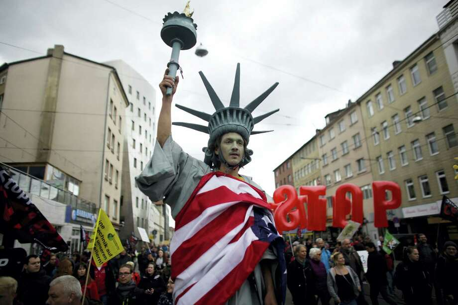 In this April 23, 2016 picture, a man walking on stilts and dressed like the Statue of Liberty attends a protest against the planned Transatlantic Trade and Investment Partnership, or TTIP, ahead of the visit of United States President Barack Obama in Hannover, Germany. Photo: AP Photo/Markus Schreiber/file   / Copyright 2016 The Associated Press. All rights reserved. This material may not be published, broadcast, rewritten or redistribu