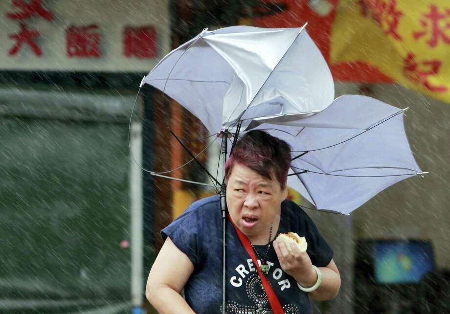 A woman eats and struggles with her umbrella against powerful gusts of wind generated by typhoon Megi across the the island in Taipei, Taiwan, Tuesday, Sept. 27, 2016. Schools and offices have been closed on Taiwan and people in dangerous areas have been evacuated as a large typhoon with 162 kilometers- (100 miles-) per-hour winds approaches the island. Photo: AP Photo/Chiang Ying-ying    / Copyright 2016 The Associated Press. All rights reserved.