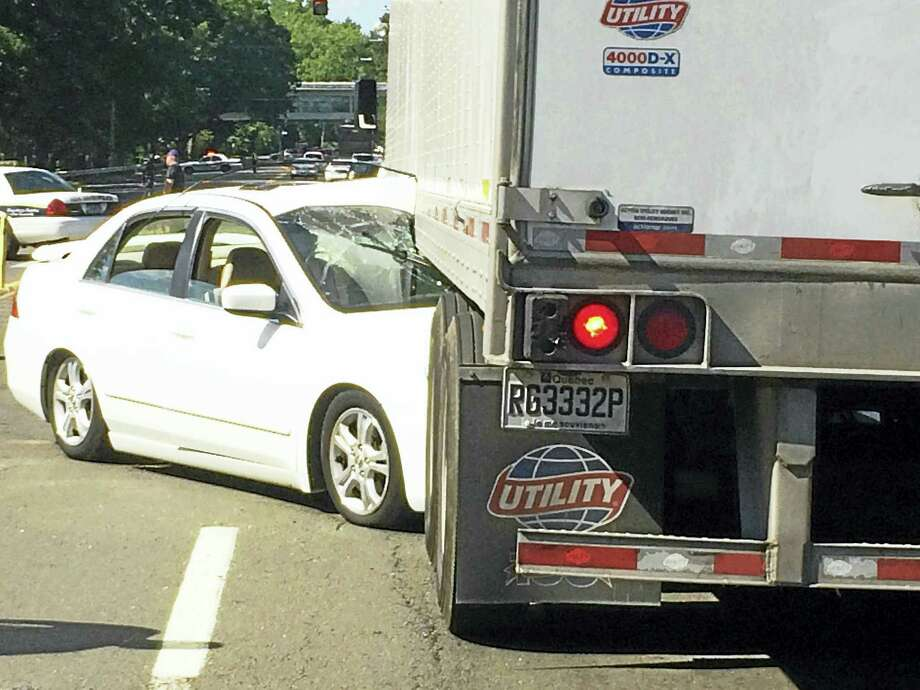 A woman was taken to the hospital Wednesday after her car slammed into a tractor-trailer on Ella T. Grasso Boulevard near the intersection with North Frontage Road. Photo: Wes Duplantier - The New Haven Register