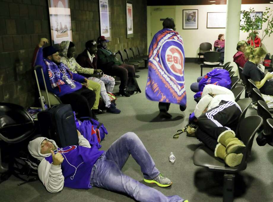 Cubs fans wait for the train after watching Game 2 of the World Series in Cleveland. About two dozen Cubs fans boarded Amtrak's Lake Shore Limited trains 49/449 at 3:45 a.m. for the 341-mile trip to Chicago's Union Station. Photo: Chris Carlson — The Associated Press   / Copyright 2016 The Associated Press. All rights reserved.