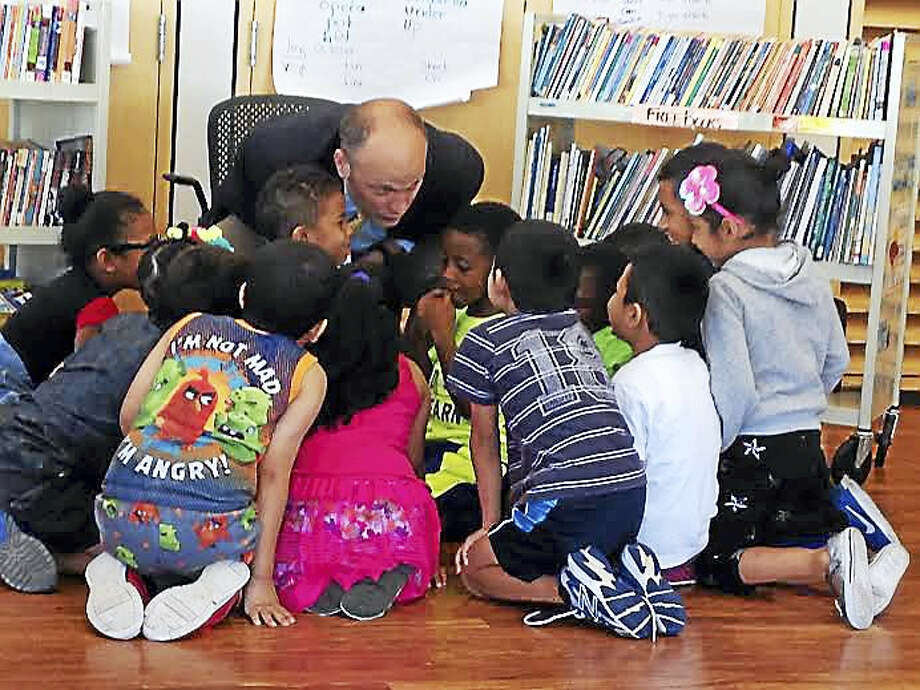 New Haven Superintendent of Schools Garth Harries whispers a message to city children to thank their New Haven Reads instructors Wednesday morning. Photo: Brian Zahn — New Haven Register
